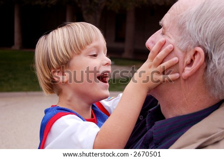 Four year old boy playing with his grandfather - stock photo