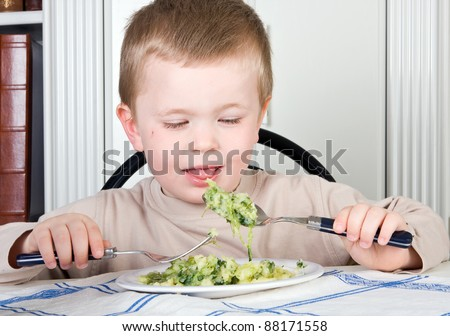 Four year old boy refusing to eat his vegetables - stock photo