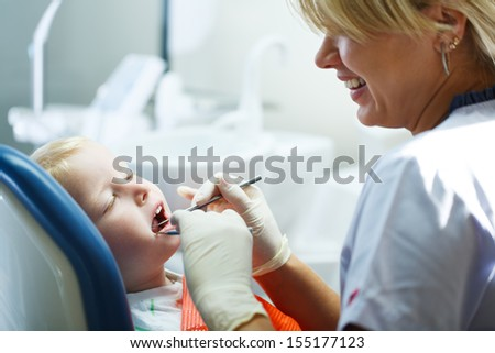 Four year old boy visits the dentist at her office for a check up. - stock photo