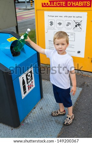 Four year old child putting waste in bin  - stock photo