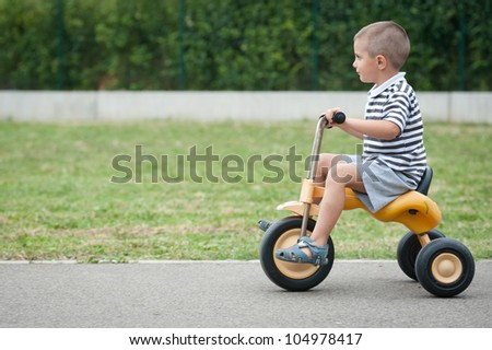 Four year old kid playing outdoor on tricycle. - stock photo