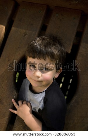 Four year old small boy with head through window of playground equipment. - stock photo