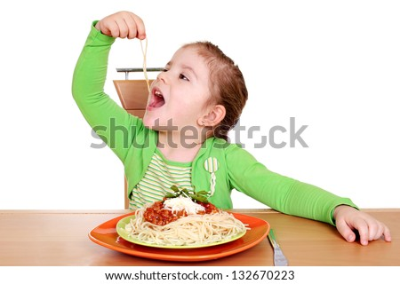 four years hungry little girl eating spaghetti - stock photo