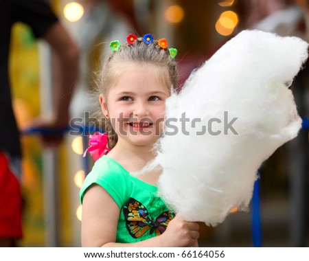 Four years old  girl with white cotton candy. - stock photo
