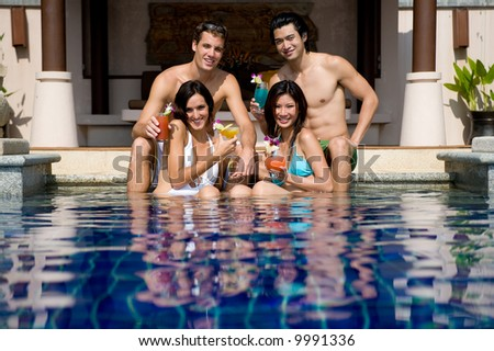 Four young adults sitting in a pool with tropical cocktails - stock photo