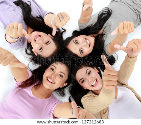 four young attractive asian women relaxing smiling lying on the floor showing thumbs up - stock photo