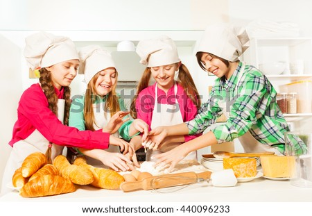 Four young bakers kneading dough at the kitchen - stock photo