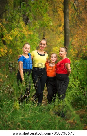 Four Young Girlfriends Hanging Out in the Forest with Autumn Colours - stock photo