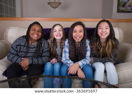 Four young girlfriends sitting on a couch at home - stock photo