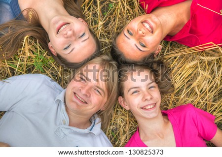Four young happy people lying on the ground - stock photo