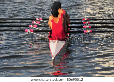 Four young men rowing  on a river - stock photo
