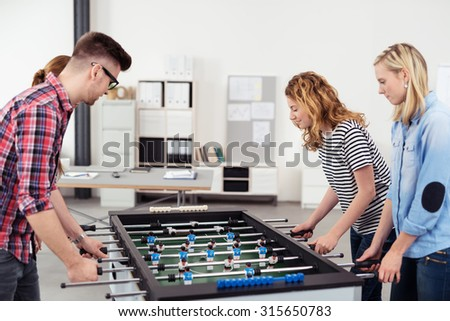 Four Young Office Workers Playing Table Soccer Game During their Break Time. - stock photo