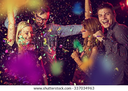 Four young people having fun and dancing at a party - stock photo