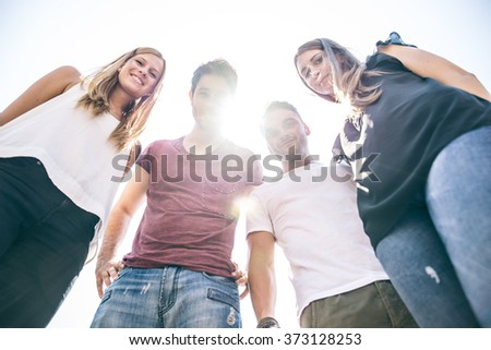 Four young people looking down at camera with backlight and sunflare - Friends smiling at camera - concepts about youth and lifestyle - stock photo
