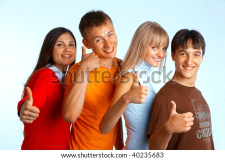 Four young people on white background laughing and giving the thumbs-up sign. - stock photo