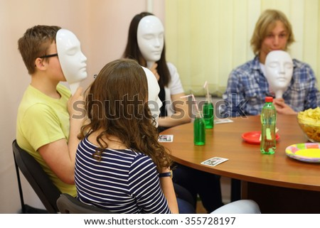 Four young people play Mafia with masks at the table in the classroom - stock photo