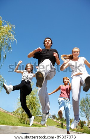 Four young people running - stock photo
