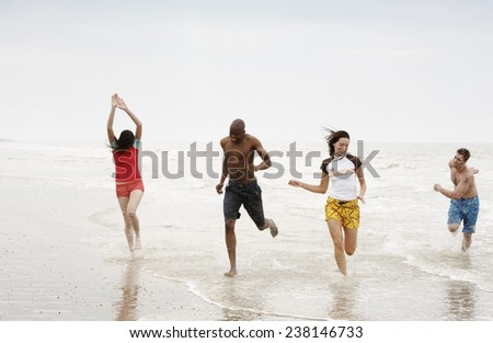 Four Young People Running in Surf - stock photo