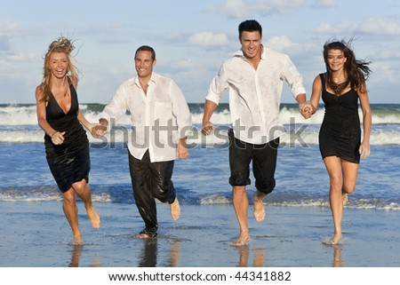 Four young people, two couples, holding hands, having fun and running in the sea on a beach - stock photo