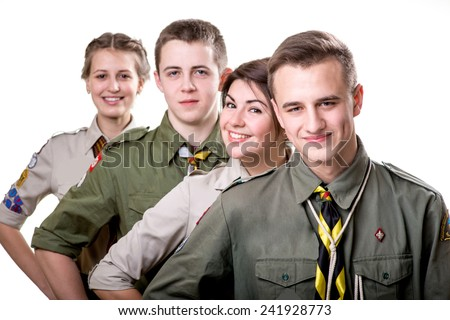 Four young scout boys standing in uniform on white background - stock photo