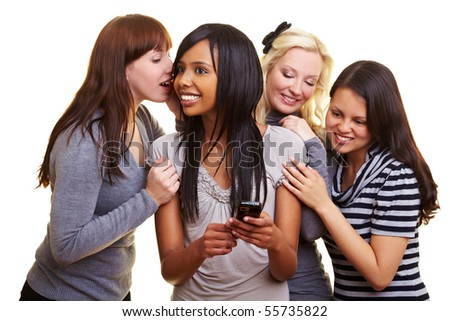 Four young women centered around a cell phone - stock photo