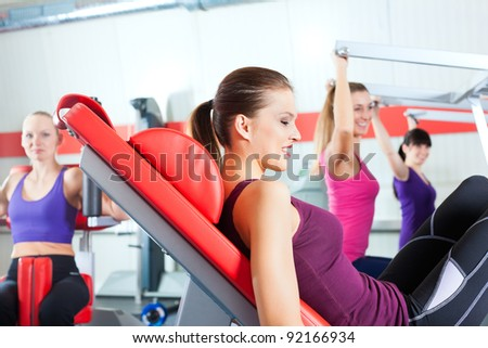 Four young women doing strength or sports training in gym for a better fitness - stock photo