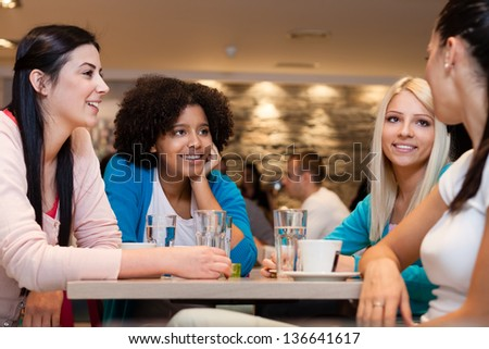 Four  young women having coffee break - stock photo