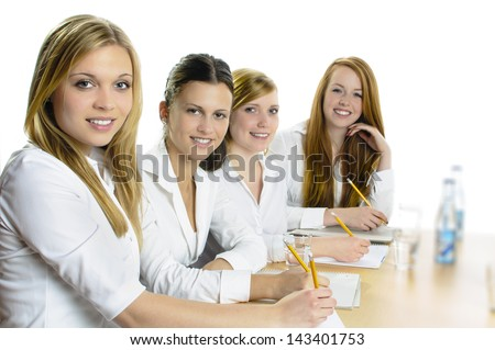 Four young women sitting at a table and hold a pencil in hand, they look happy in the camera, isolated against a white background. - stock photo
