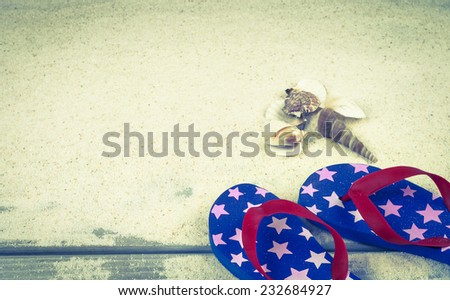Fourth of July Rubber Sandal Flip-Flop Thongs and seashells on Wood Boardwalk and White Sand background with room or space for copy, text, your words.  Vintage instagram, horizontal warm tone  - stock photo