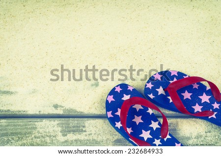 Fourth of July Rubber Sandal Flip-Flop Thongs on Wood Boardwalk and White Sand background with room or space for copy, text, your words.  Vintage instagram, horizontal warm tone  - stock photo