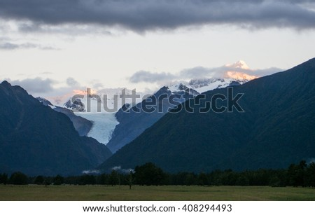 Fox Glacier and mountains of New Zealand - stock photo