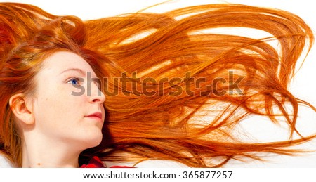 foxy hair, carrots. Portrait of beautiful redhead girl with red lipstick on her lips. Beautiful girl with long shiny hair. Hair decomposed on a white floor - stock photo