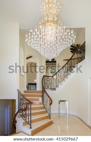 Foyer in luxury home with circular staircase and chandelier. - stock photo