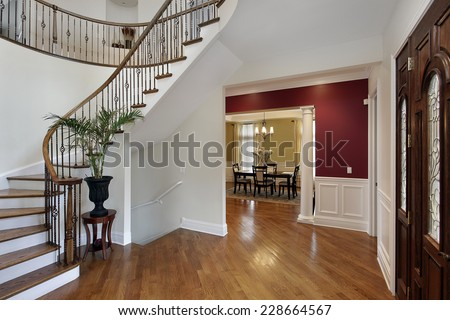 Foyer in luxury home with curved staircase and view into dining room - stock photo