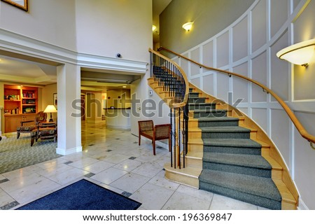 Foyer with columns and wooden staircase. Open floor plan. - stock photo