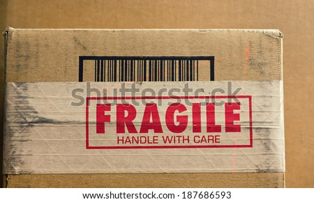 Fragile sign on shipping box with barcode being read by a thin red laser. - stock photo