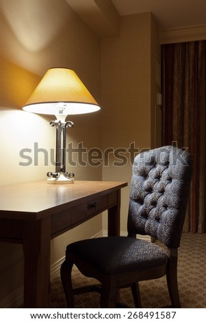 fragment like view of dim lighted interior  with  desk and chair - stock photo