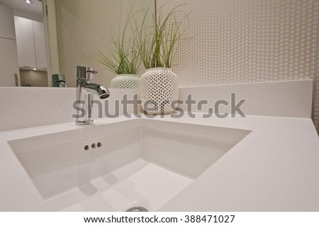 Fragment  of a bathroom, washroom with washbasin (sink) and the vase as a decorative element on the counter. Interior design. - stock photo