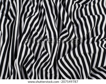 Fragment of a striped wrinkled black and white piece of a cloth fabric as a background texture - stock photo