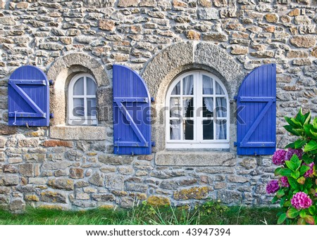 Fragment of a typical country house with blue shutters in Brittany, France - stock photo