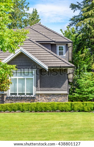 Fragment of a very neat and colorful home with gorgeous outdoor landscape in suburbs of Vancouver, Canada. - stock photo