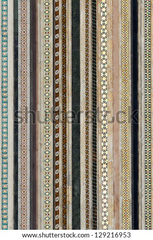 Fragment of a wall of a cathedral (Duomo) with parallel vertical mosaic strips, Orvieto, Umbria, Italy - stock photo