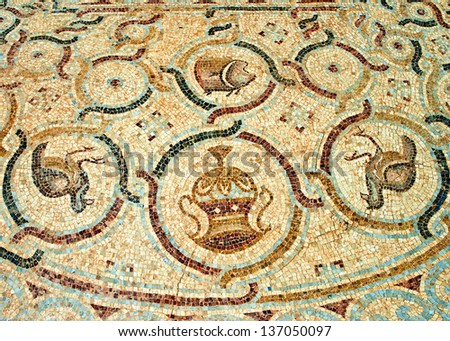 Fragment of an ancient  floor mosaic. Colorful small tiles, images of the animals and birds, floral ornament. Antique synagogue. Israel - stock photo