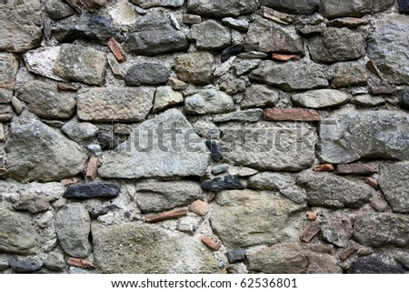 Fragment of an ancient stone wall - stock photo