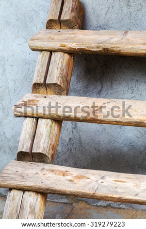 fragment of an old wooden stairs at the concrete wall - stock photo