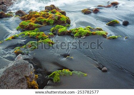 Fragment of black sand and waves - stock photo