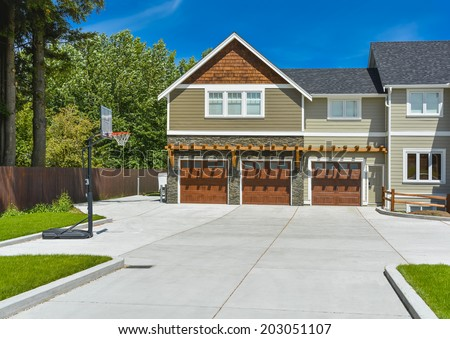 Fragment of brand new farmer's house with three garage doors and concrete driveway in front and blue sky background. Basketball ring in front of huge farmer's house. - stock photo