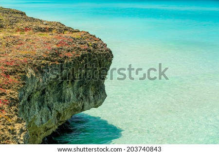 fragment of cliff sitting in turquoise charming clear Atlantic ocean water background - stock photo