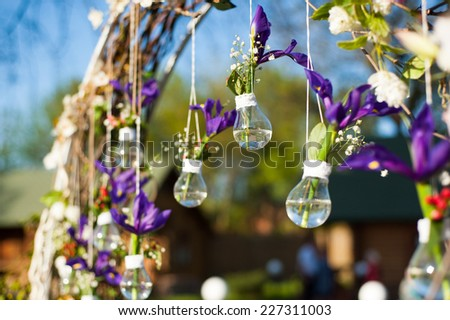 Fragment of creatively decorated wedding arch with lamps and living flowers outdoors - stock photo