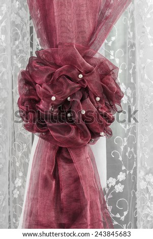 Fragment of decoration window curtain against a white tulle closeup - stock photo